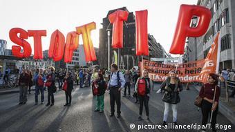 En una protesta en el centro de Bruselas, manifestantes portan gigantes letras rojas que dicen Stop TTIP