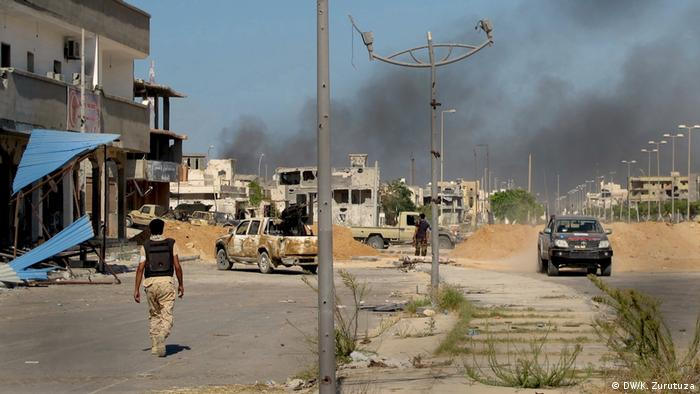 A could of black smoke rises on the horizon over Sirte.