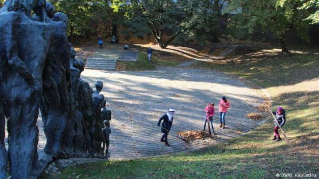 Школьники убирают листву на территории мемориала Яма в Минске