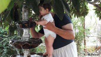 Abou Hadi with his child in his garden in al-Waer Syria