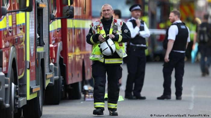 A firefighter stands near fire trucks outside Grenfell Tower (Picture alliance/dpa/S. Paston/PA Wire)