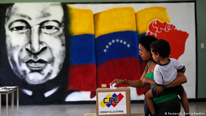 A woman holds her infant as she casts her vote in front of a mural of the late Venezuelan President Hugo Chavez