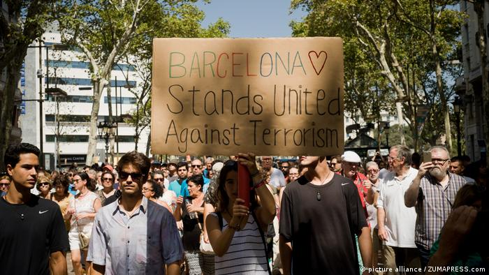 A woman holds a sign reading: Barcelona stands united against terrorism