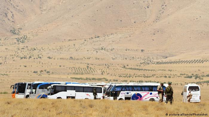 A convoy of buses prepare to evacuate Islamic State militants and their families from Qara