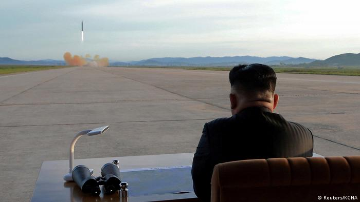 North Korea's Kim Jong Un looking out at runway (Reuters/KCNA)