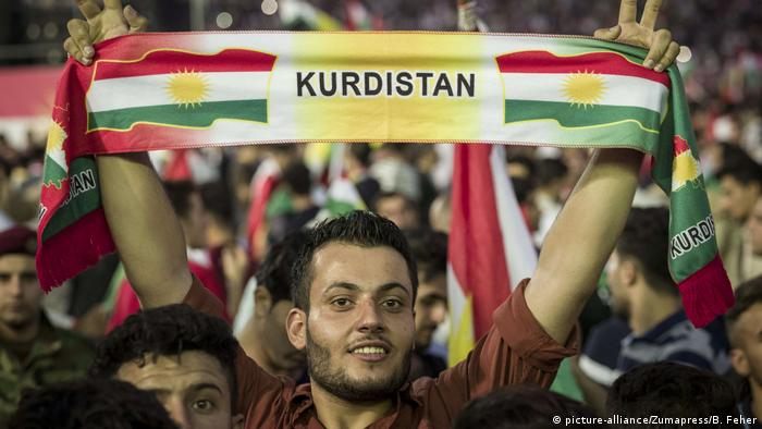 A person smiling and holding a banner that reads Kurdistan at a rally (picture-alliance/Zumapress/B. Feher)