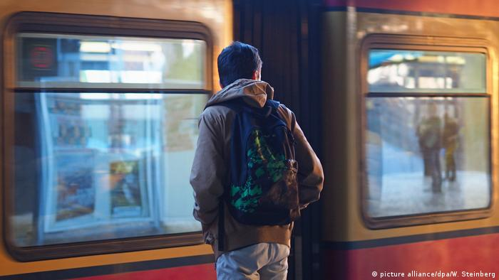 A young migrant with a backpack waits for a train in Berlin (picture alliance/dpa/W. Steinberg)