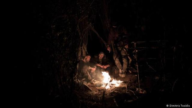Refugees gather around fire
