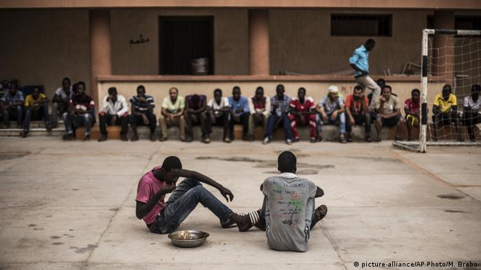 A migrant finishes his lunch while others wait to return to their barracks, at a detention center for migrants (AP Photo/Manu Brabo)