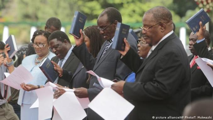 A group of ministers that make up Zimbabwe's new cabinet sworn in in December read their oaths of office – each holding documents in one hand and a bible held high in the other. (picture alliance/AP Photo/T. Mukwazhi)