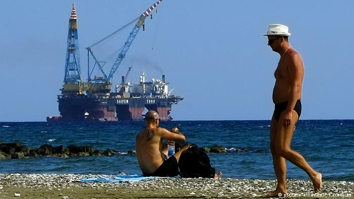 A man walks as an other man sits on a beach as a drilling platform is seen in the background outside from Larnaca port