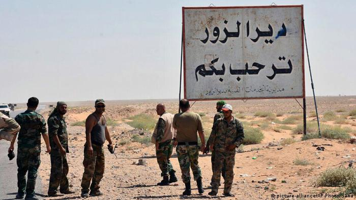 Syrian troops and pro-government gunmen standing next to a sign in Arabic which reads, Deir el-Zour welcomes you, in the eastern city of Deir el-Zour, Syria.