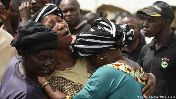 Three women wearing cry as they embrace each other (Getty Images/P. Utomi Ekpei)