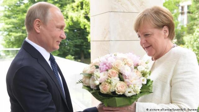 Putin welcomes Merkel with flowers in 2018 (picture-alliance/Sputnik/S. Guneev)