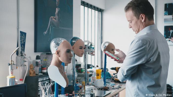 A man faces female robot faces in a lab and looks at his cell phone.  (Kloos & Co. Media)