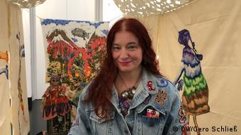 Picture of the artist Delaine Le Bas in front of her installation Witch Hunt who looks like a tent with figures and patterns