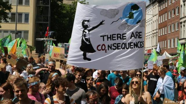 A banner at a protest reads There are Co2nsequences