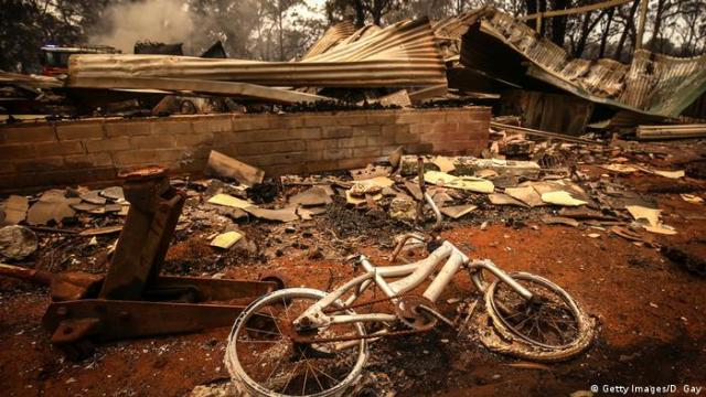 A charred bicycle in front of the remains of a house destroyed by bushfire
