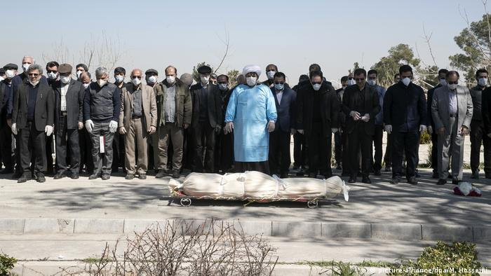 A row of men wearing masks line up with their heads bowed while a man in blue scrubs, mask and headdress looks down to a body wrapped in a shroud.