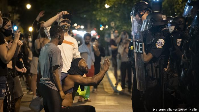 A man pleads with officers as crowds protesting the killing of G. Floyd clash with police in the blocks just north of the White House