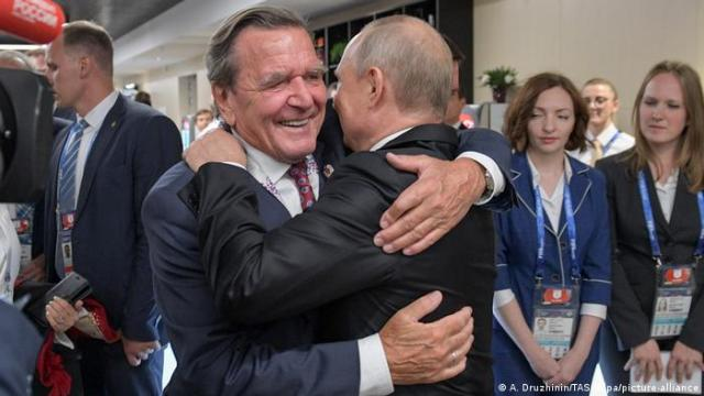 Russia's President Vladimir Putin and Gerhard Schroeder hugging each other at the opening of the 2018 FIFA World Cup (TASS/dpa)