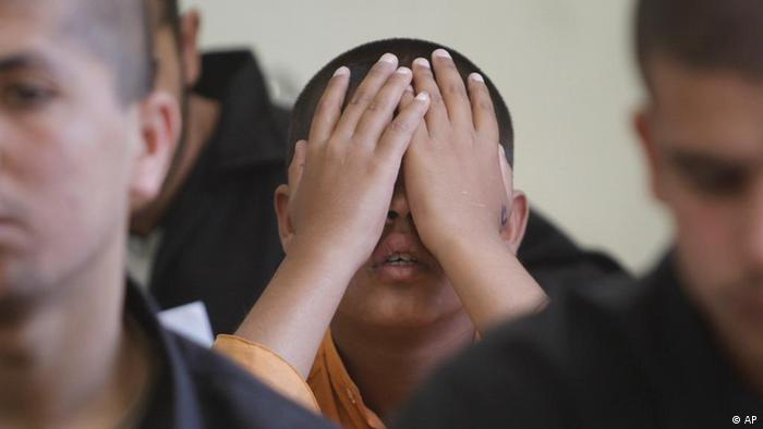 A child of Middle Eastern descent covers his face with his hansd in a crowded classroom
