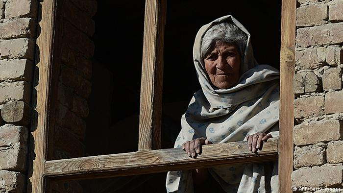 A elderly Afghan woman looks through the window of her house (Phtoto: AFP)