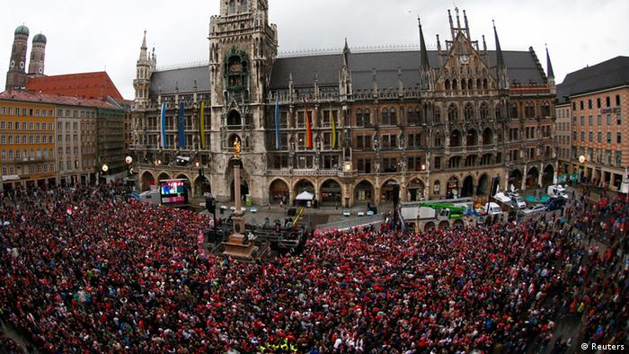 Bayern Munich supporters wait for the Bayern team with the German soccer championship trophy during a reception at Munich's townhall May 11, 2013. Bayern held their 23rd German league title on Saturday after a comfortable 3-0 over Augsburg as they prepare for the all-German Champions League final against Borussia Dortmund in two weeks. REUTERS/Michaela Rehle (GERMANY - Tags: SPORT SOCCER)