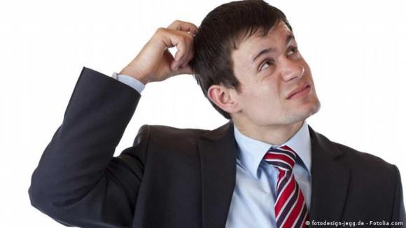 A man in a suit is scatrching his head because he's confused