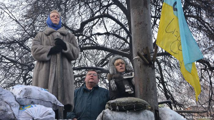 A Ukrainian woman stands at one barricade, with two individuals standing near her<br /><br /> (c) DW/R. Goncharenko