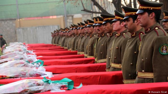 Soldiers stand next to coffins covered with the Afghan flag (Foto: Hussain Sirat/DW)