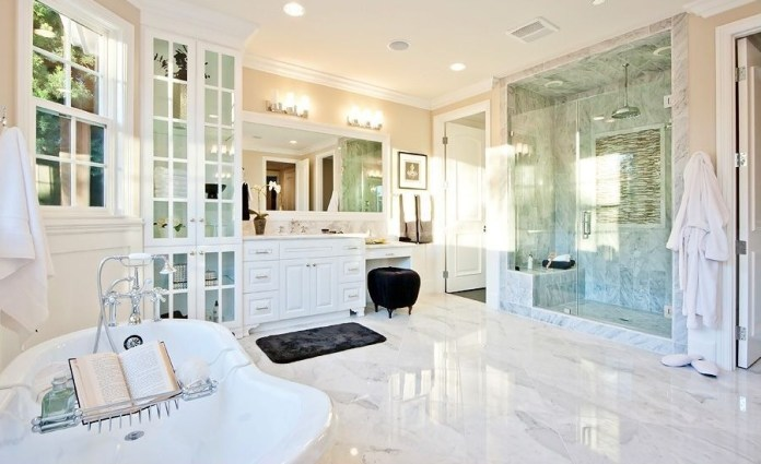 Marble flooring anchors this bright bathroom, featuring full height glass door cabinets next to a