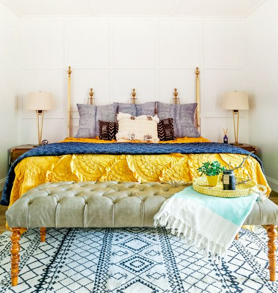 Eclectic bedroom with blue and yellow bedding, tufted bench, throw, and patterned rug