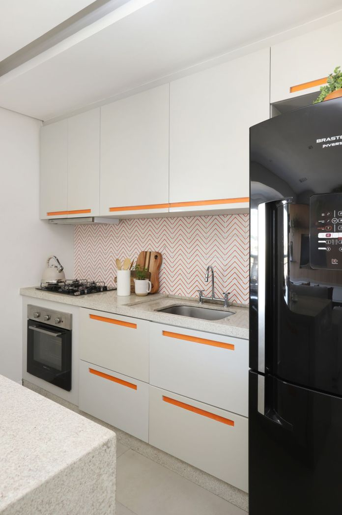 Environment with orange decor and black refrigerator