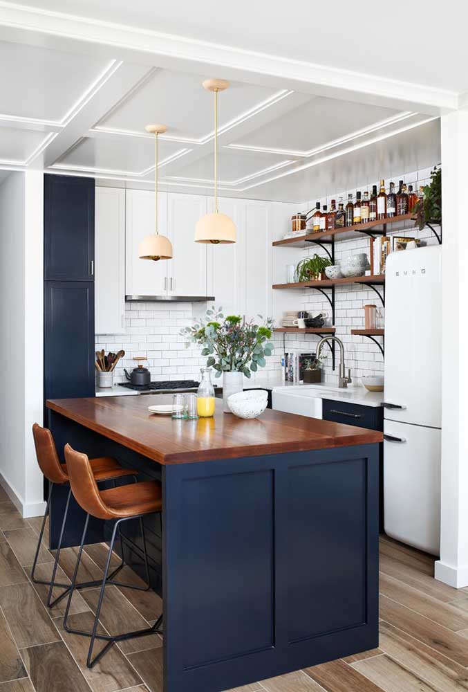 13. This small American kitchen looks amazing with the blue hue and the shape of the wider counter so that it looks like a dining table