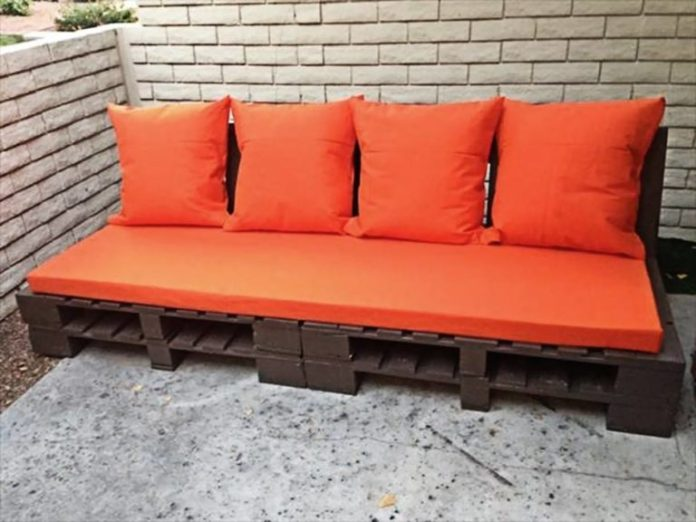 15. Brown pallet sofa with red cushions