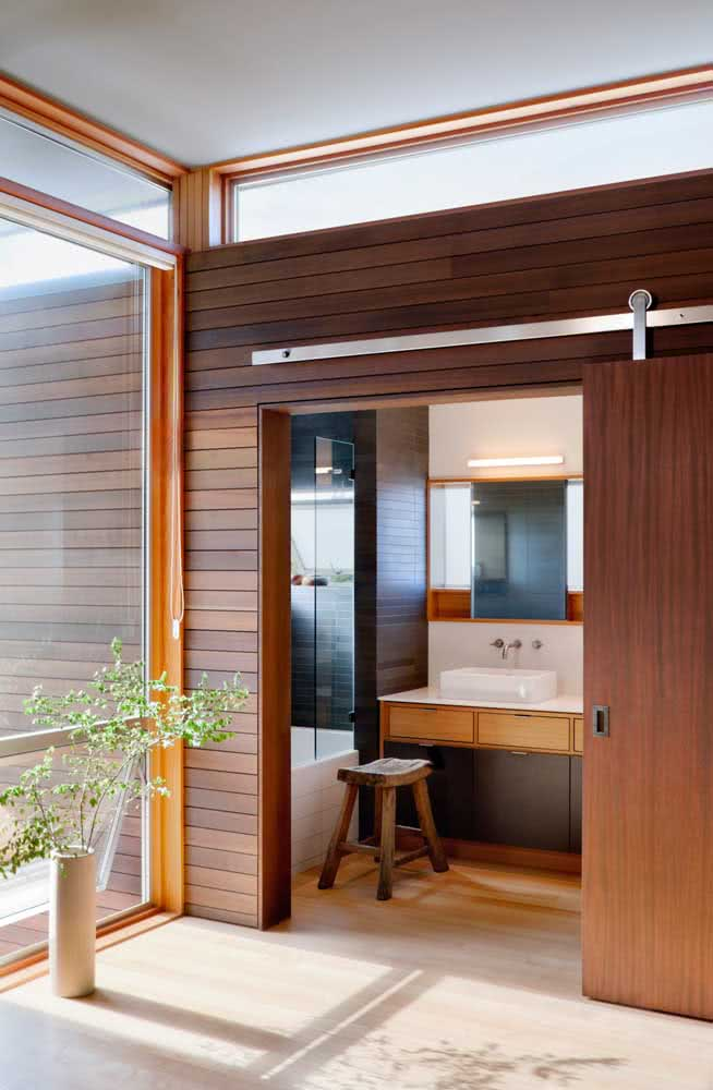 26 - Wooden sliding door for the bathroom. Highlight for the wall that is also covered in wood.