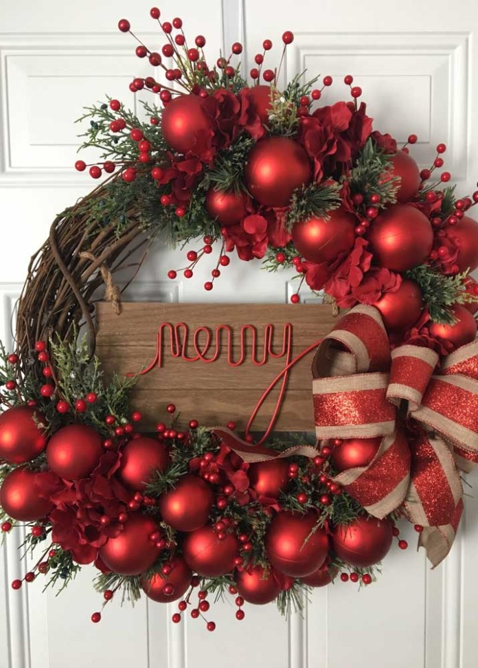 29. This other wreath features the typical Christmas red to decorate the wreath with a base of tree branches.