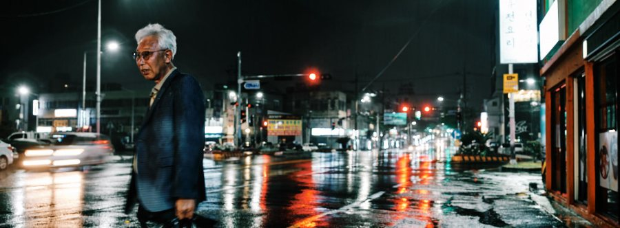 Old man waits for a taxi on a rainy night