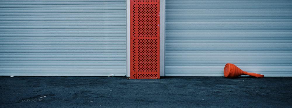 Orange traffic cone in front of blue door