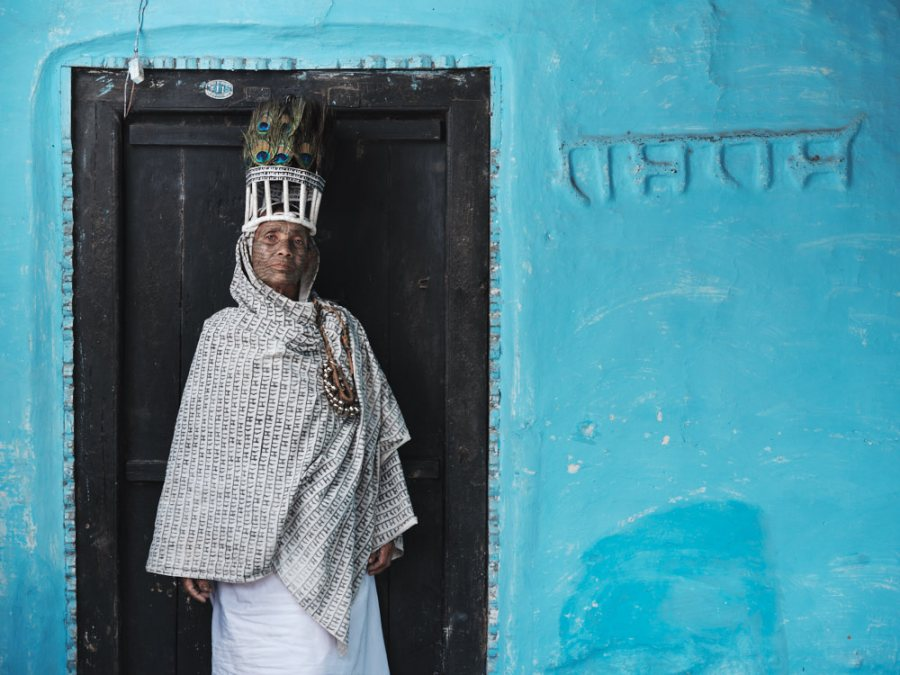 A Ramnami woman stands in front of her house in a small village in Chhattisgarh