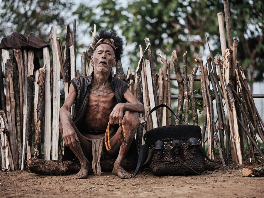 A Wancho headhunter sits with his basket