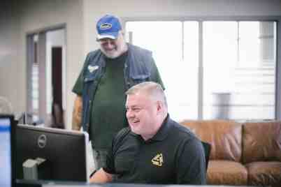 Member of the Truck Driver community standing near a Dynamic Transit worker at a desk.