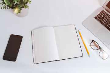 open white notebook near pencil and eyeglasses beside laptop computer on white surface