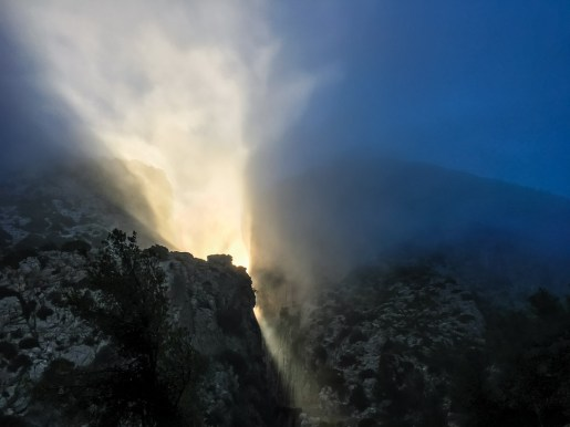 The early morning sun shoots rays of light through the narrow gorge