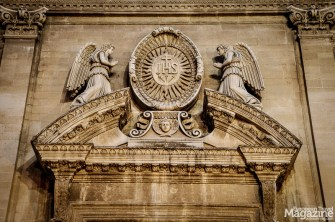 The broken tympanum shows the emblem of the Society of Jesus protected by two angel