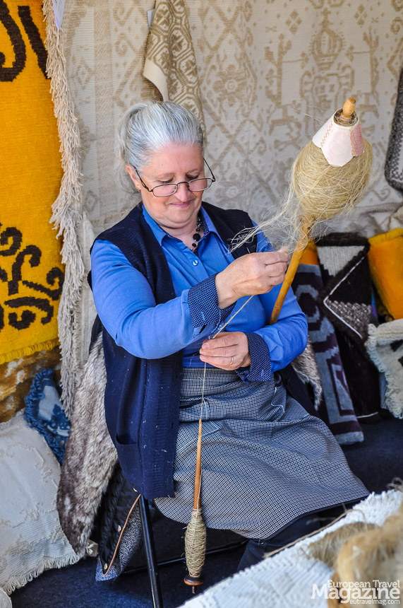 The lovely lady opposite the stall of Julieta spins flax with her hands.