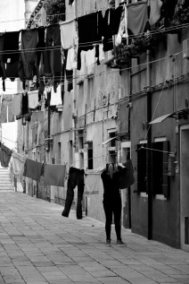 A Venetian woman calmly hangs laundry in a quiet morning
