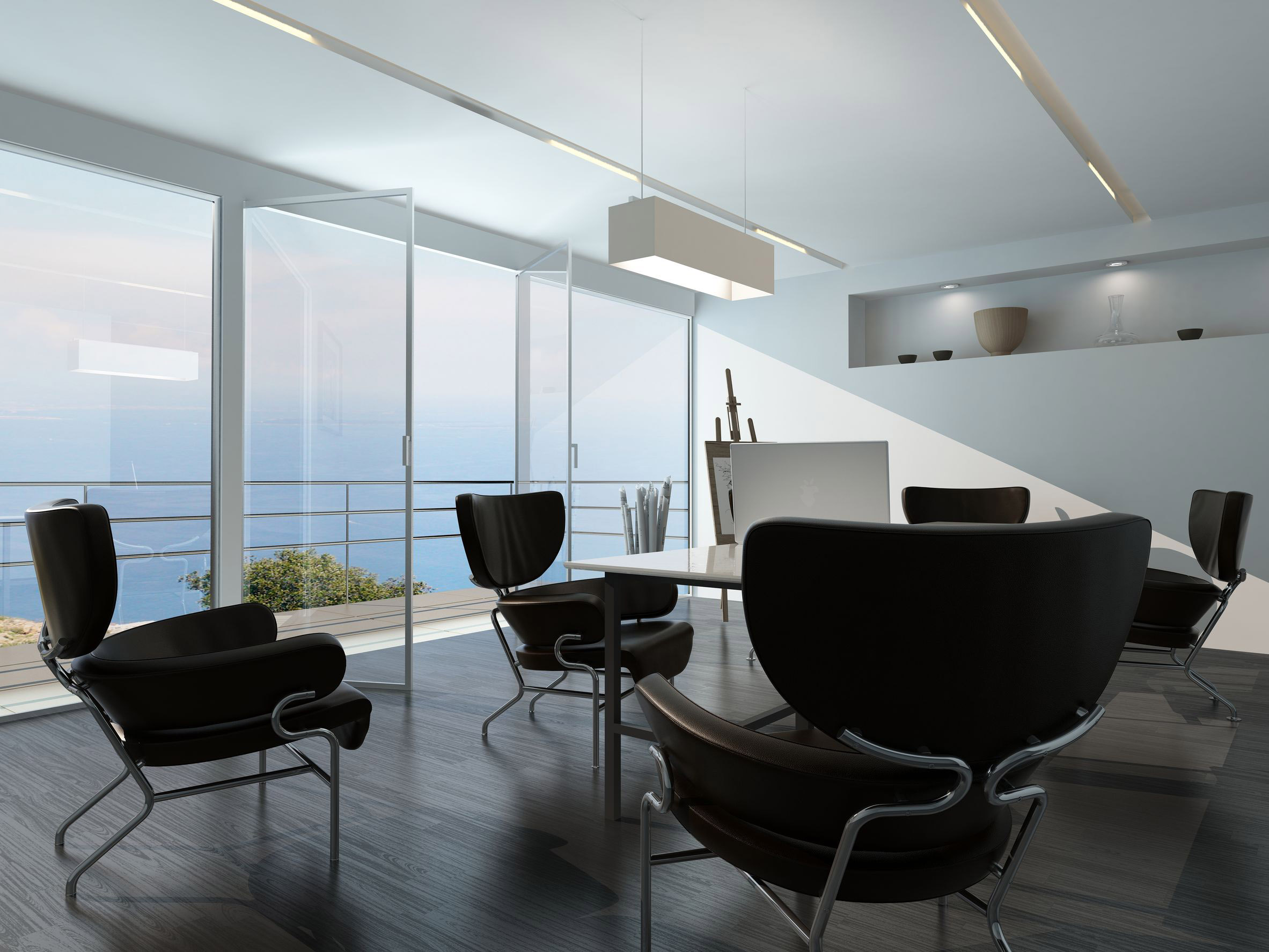 contemporary office conference room interior with scattered armchairs around a central table in front of a glass wall overlooking the ocean and an easel on a stand in the corner
