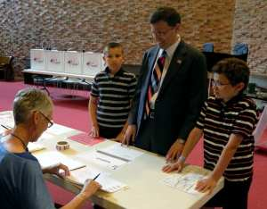 Steve Wells with his sons Jack and Sam preparing to vote at St. James Church in Cazenovia on June 28. Photo by Jason Emerson